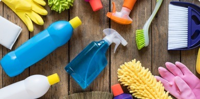 cleaning products in plastic containers lying flat on a wooden surface