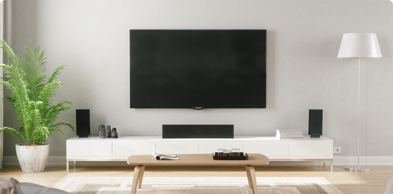 a flatscreen television on the wall in a lounge setting, with a low coffee table and a plant in frame