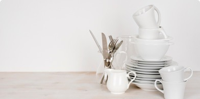 clean, white plates, bowls and mugs stacked with cutlery to the side