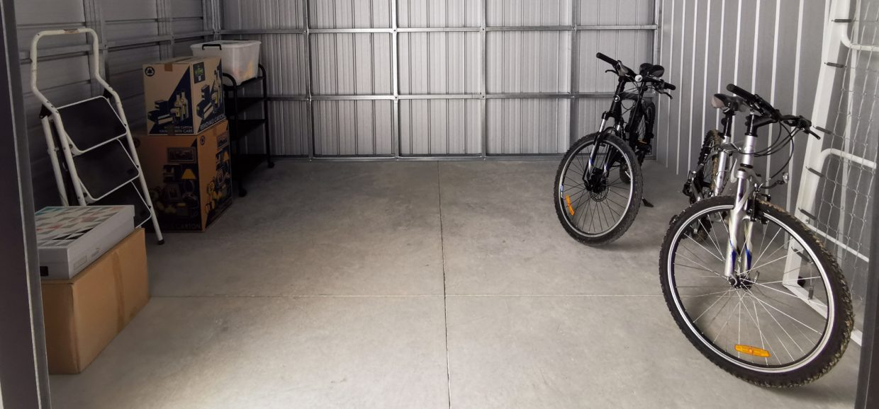 storage units, with the shutter to one being open and inside two bikes in view