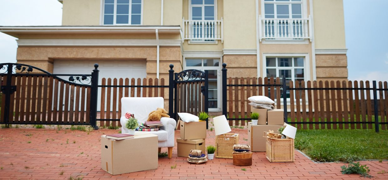 Boxes and personal possessions on the driveway outside a house with a wooden fence