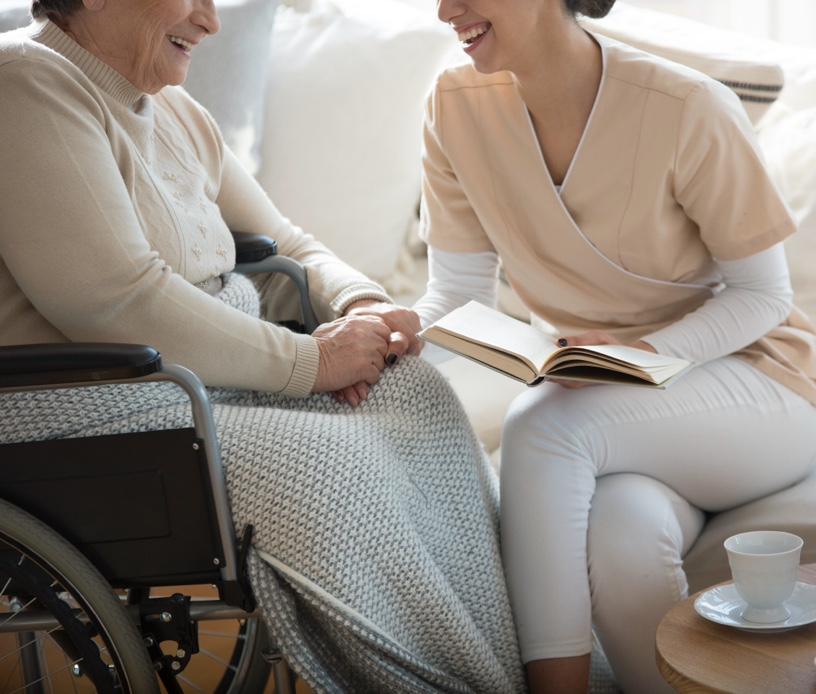 An elderly woman sits in a wheelchair as a younger woman reads a book to her