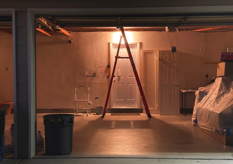 A ladder in a room with a single light